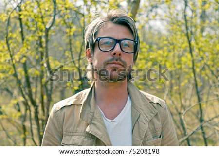 Young casual man with glasses standing in nature. - stock photo