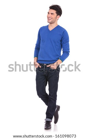 young casual man with hands in pockets looking away from the camera to his side - stock photo