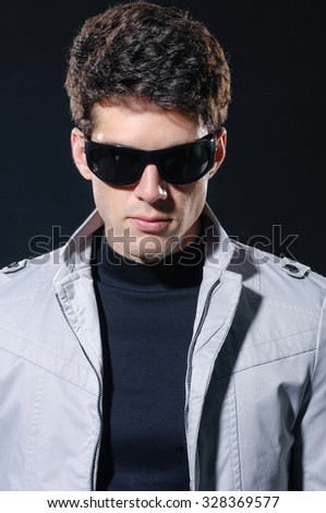 young casual man with sunglasses portrait, isolated over black background - stock photo