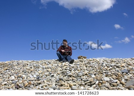 Young casual man working with touch pad at the beach - stock photo