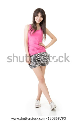 Young casual pretty Asian woman in pink singlet and striped shorts. Isolated on the white background. - stock photo