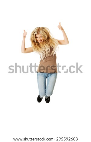 Young casual student jumping with thumbs up. - stock photo