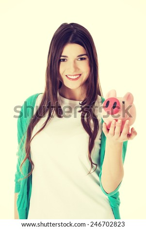 Young casual student woman holding piggy-bank.  - stock photo