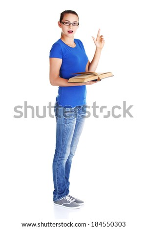 Young casual student woman with book and pointing up. Isolated on white. - stock photo