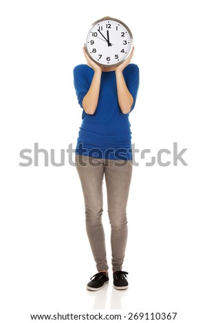 Young casual woman hiding behind a clock.  - stock photo