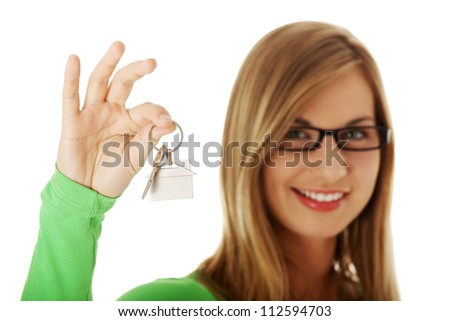 Young casual woman holding house key; isolated on white - stock photo
