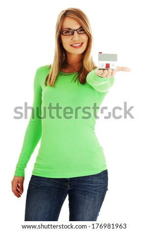 Young casual woman holding house model; isolated on white - stock photo