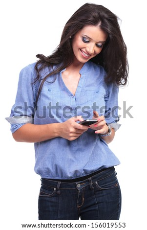 young casual woman looking at her phone and smiling. on white background - stock photo
