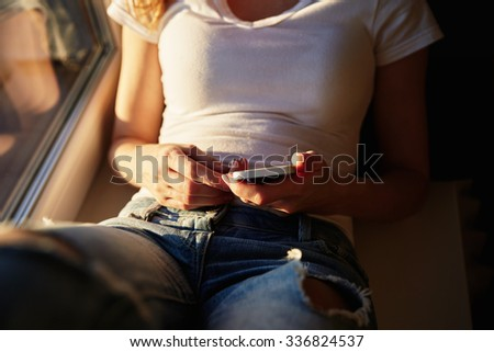 young casual woman using smart phone  at home  - stock photo
