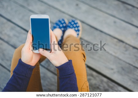 young casual woman using smart phone on the beach - stock photo