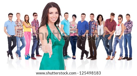 young casual woman welcoming you with a handshake in front of her large team - stock photo