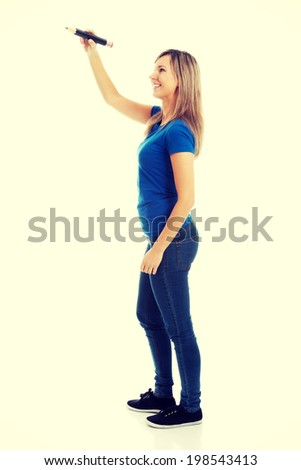 Young casual woman writing on copy space - stock photo