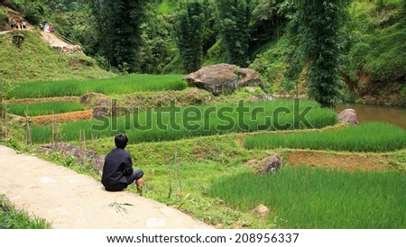 Young Cat Cat child sitting near terraced rice field in Sapa, Vietnam - stock photo
