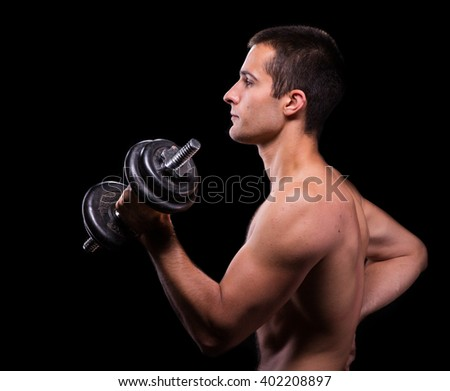 Young caucasian athlete working out, holding dumbbell, photo on black background, side view - stock photo