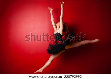 Young Caucasian ballerina executing a jump against bright red wall, throwing her hands in the air - stock photo