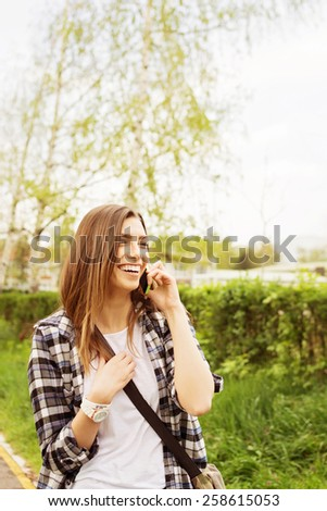 Young Caucasian blonde woman speaking on smartphone outdoors in spring laughing. Casual teenage girl in park talking on the phone. Vertical, retouched, natural light. - stock photo