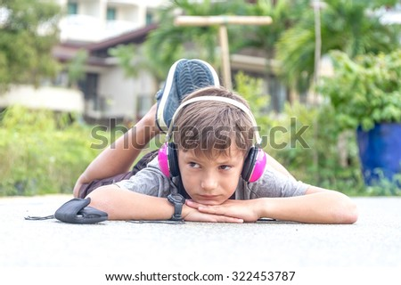 young caucasian boy listening to music via headset on natural background - stock photo