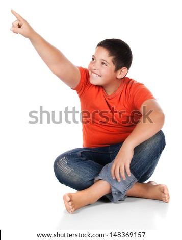 Young caucasian boy wearing an orange t-shirt and blue jeans. The boy is pointing with his finger and looking away from the camera. - stock photo