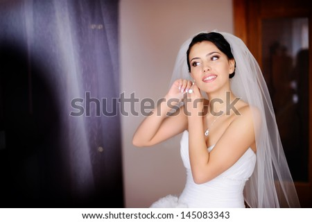 young caucasian brunette bride is getting ready in  the morning - stock photo