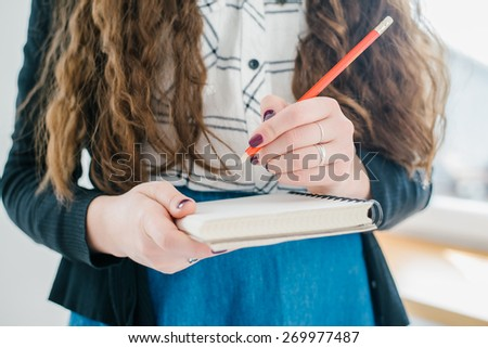 young caucasian brunette haired happy smiling business woman holding diary and red pancil - stock photo