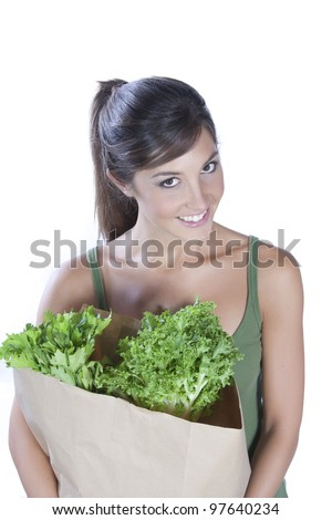 young caucasian brunette holding a bag of vegetables - stock photo