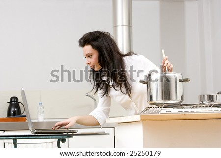 young caucasian brunette working with laptop while cooking in her kitchen.Concept of online receipt,hard working. - stock photo