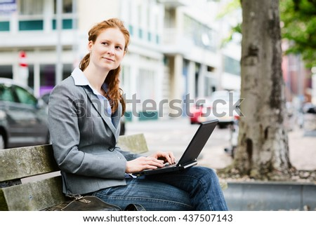 Young Caucasian business entrepreneur using a laptop computer on a quiet city street. - stock photo