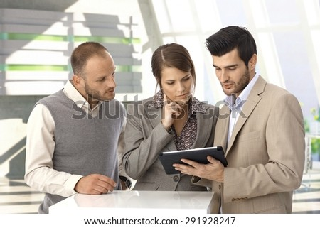 Young caucasian business people with tablet computer at office lobby. Standing, looking at screen, wearing suit. - stock photo