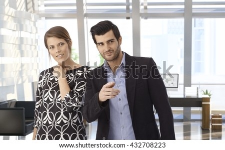 Young caucasian businessman and wife visiting bank office. Smiling, curious, pointing at something. Copyspace. - stock photo