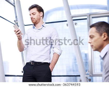 young caucasian businessman checking messages on mobile phone in modern office. - stock photo