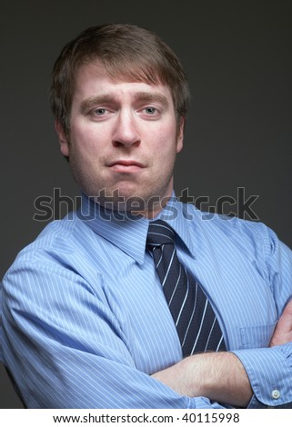 Young caucasian businessman funny expression on dark background - stock photo