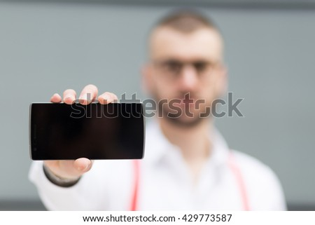 Young caucasian businessman holding smartphone. Selective focus and copy space - stock photo