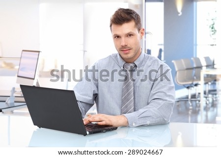 Young caucasian businessman in shirt and tie sitting at office desk using laptop looking up at camera. - stock photo