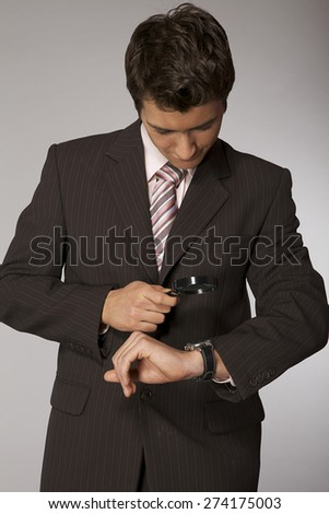 Young caucasian businessman looking on his watch with magnifying - stock photo