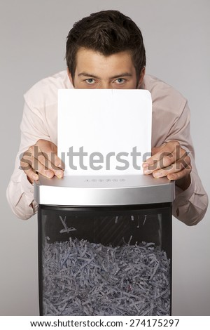 Young caucasian businessman shredding documents - stock photo