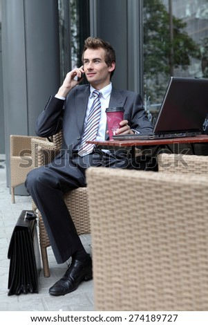 young caucasian businessman using his laptop in cafe - drinking - stock photo
