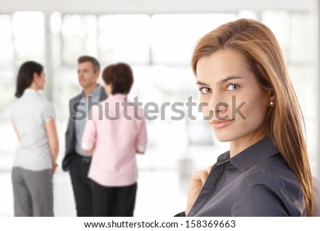 Young caucasian businesswoman at office looking at camera people talking in background. - stock photo