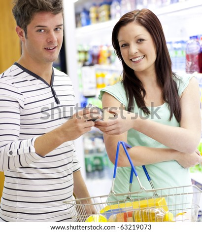 Young caucasian couple buying shampoo standing in a department of a supermarket - stock photo