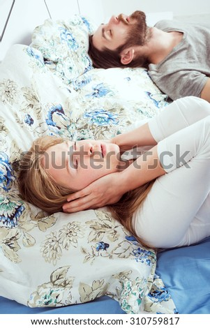 young caucasian couple in bed. male snoring and female can not sleep - stock photo