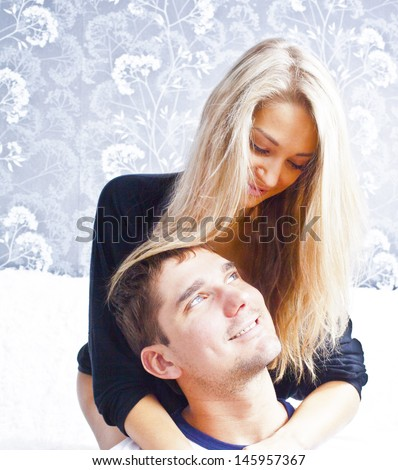 Young caucasian couple sitting, hugging, laughing on sofa Copy space for inscription  - stock photo