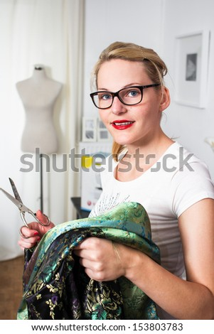 Young caucasian fashion designer with scissors in hand and mannequin in the back - stock photo