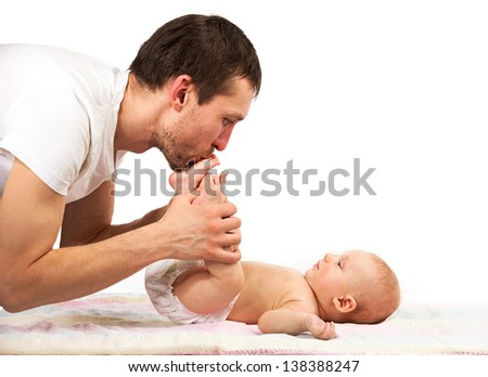 Young Caucasian father kissing feet of his baby son - stock photo