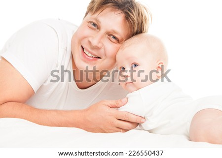 Young Caucasian father playing with baby son over white background - stock photo