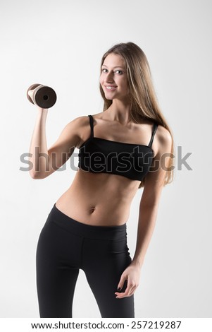 Young caucasian female athlete doing dumbbell curls with steel freeweights, muscle training with weight lifting - stock photo