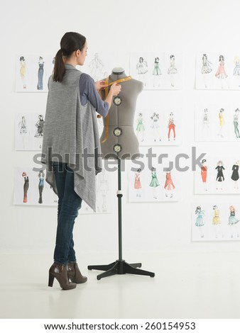 young caucasian female fashion designer taking measurements on mannequin in her studio - stock photo