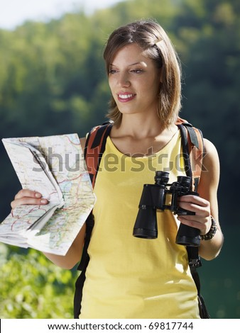 young caucasian female hiker reading map and holding binoculars. Vertical shape, waist up, front view - stock photo