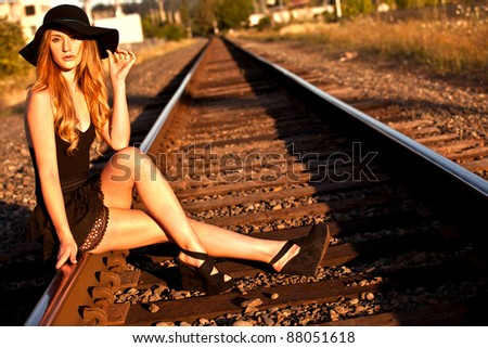 Young caucasian female model posing on railroad tracks with a large black hat. - stock photo