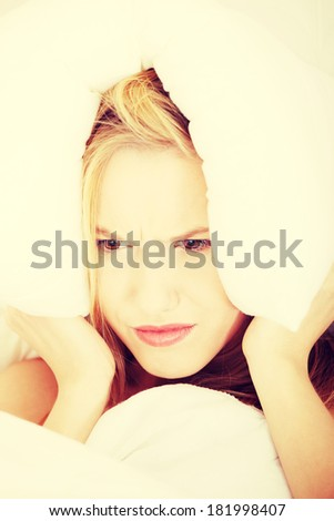 Young caucasian female on bed with pillow on her head. Insomnia concept - stock photo
