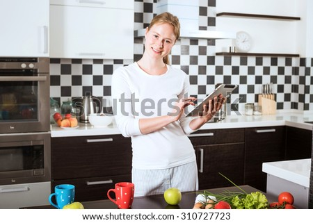 young caucasian female on kitchen with apple and tablet. Woman on kitchen searching on tablet recipes of healthy food. Cooking healthy food with vegetables and fruits - stock photo
