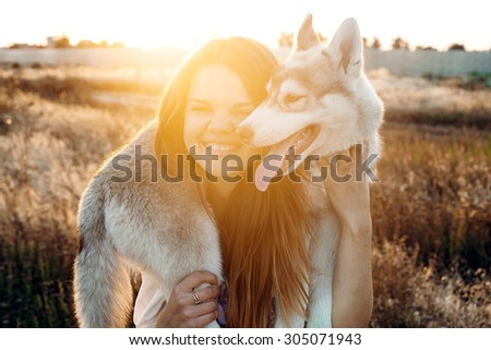 young caucasian female playing with her siberian husky puppy in the field during the sunset. Happy smiling girl having fun with puppy outdoors in beautiful light - stock photo